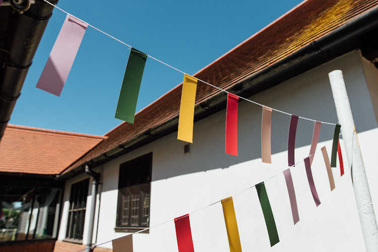 Ticker Tape Bunting Alternative Colourful Outdoor Humanist Village Hall Wedding http://www.chebirchhayesphotography.com/