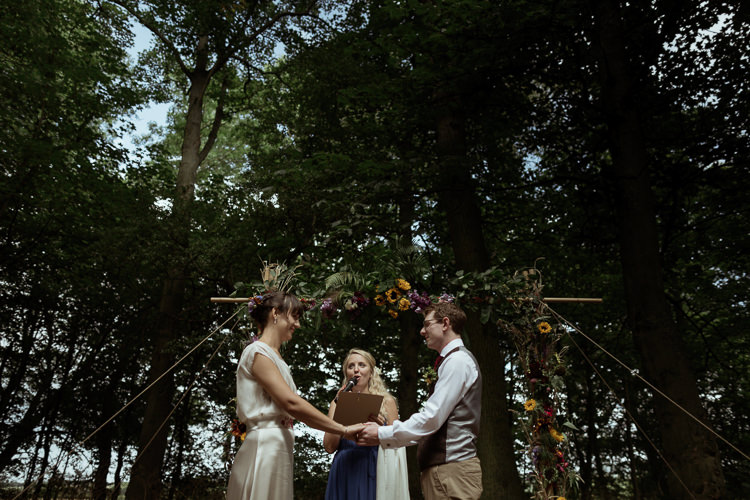 Vows Bamboo Ceremony Structure Floral Flowers Foliage Bespoke Bride Waisted Belt Tweed Groom Waistcoat Chinos Magical Woodland Clearing Colourful Tipis Wedding https://www.lukebellphotography.co.uk/
