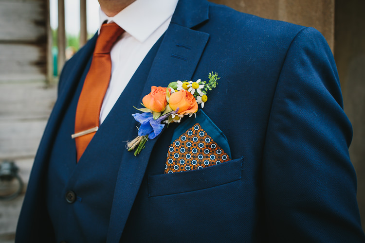 Navy Three Piece Suit Waistcoat Groom Silk Pocket Square Buttonhole Wildflower Daisy Orange Tie Small Colourful Cool Alternative Wedding https://www.alexapoppeweddingphotography.com/