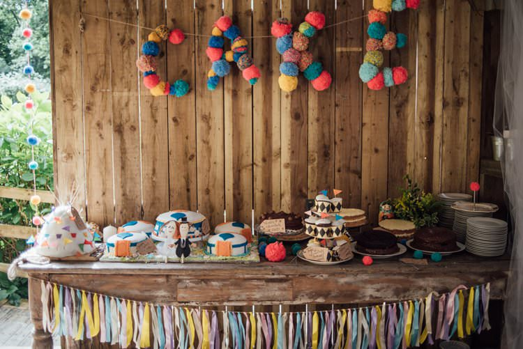 Cake Table Pom Pom Sign Tassels Multicolour Rustic Wooden Adventurous Festival Bohemian Wedding https://libertypearlphotography.com/