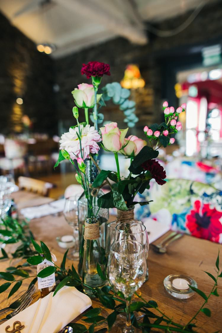 Mismatched Jars Bottles Roses Foliage Flowers Twine Colourful Floral Family Friendly Wedding http://www.sallytphoto.com/