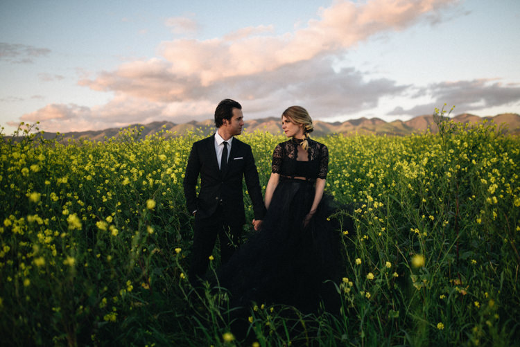 Dark Moody Black Dress Bride Lace Sleeves Outdoor Field Flowers | Edgy Emerald City Wedding Ideas http://www.yvonnegollphotography.com/