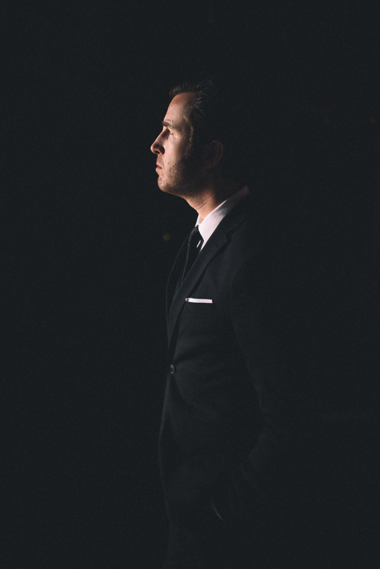 Dark Moody Black Suit Groom Light Silhouette | Edgy Emerald City Wedding Ideas http://www.yvonnegollphotography.com/