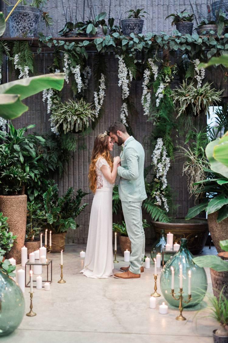 Greenhouse Wild Foliage Candles White Green Couple Embrace Palm | Greenery Botanical Wedding Ideas https://lisadigiglio.com/