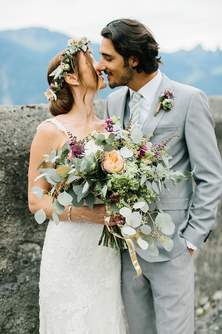 Beautiful Destination Mountains Summer Kiss Bride Groom Wild Bouquet Grey Suit | Romantic Castle Switzerland Wedding http://kbalzerphotography.com/