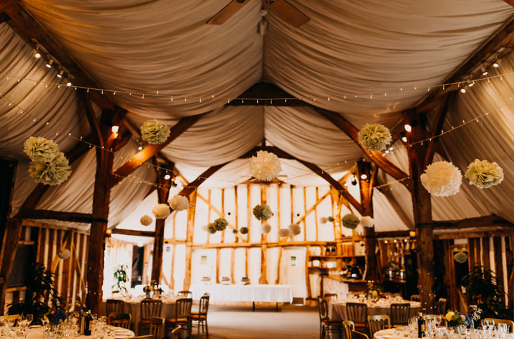 Informal Decor Paper Pompom Fairy Lights Draping Wooden Beams | Rustic Relaxed Cornflower Blue Barn Wedding http://www.peterhugophotography.com/