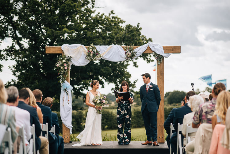 Wooden Arch Backdrop Ceremony Fabric Drapes Flowers Festival Bohemian Glamping Wedding https://theshannons.photography/