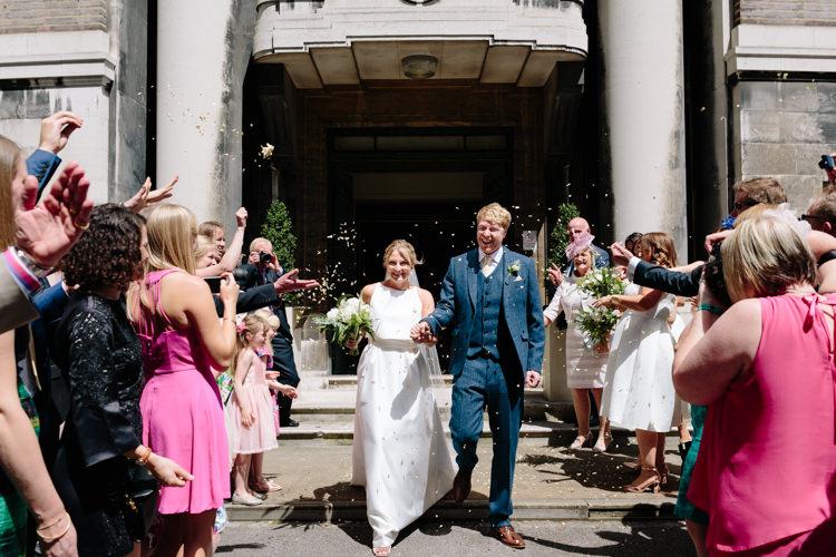 London Stoke Newington Town Hall Aisle Civil Ceremony Bride Groom Celebrate Confetti Shot | Modern Tropical Gold Urban Wedding https://www.christinewehrmeier.com/