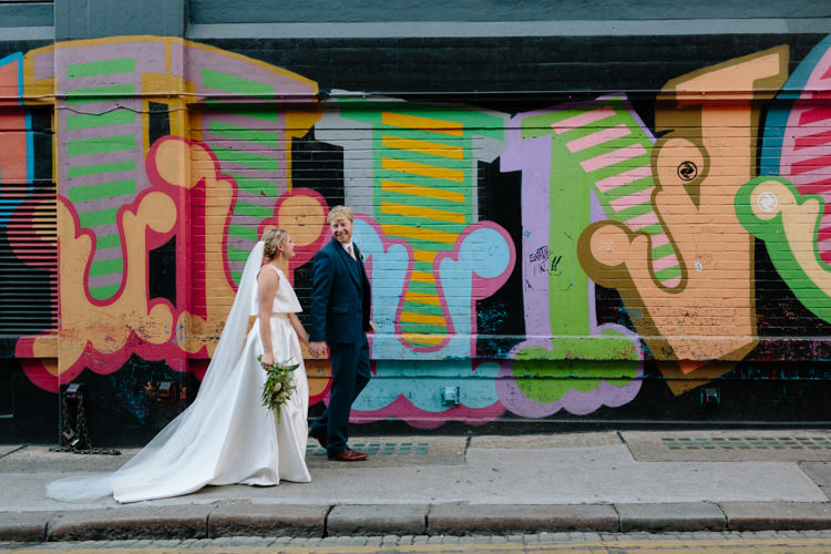 London City Bride Groom Buildings Graffiti Wall Street Foliage Greenery White Bouquet Jesus Peiro Dress Navy Suit | Modern Tropical Gold Urban Wedding https://www.christinewehrmeier.com/
