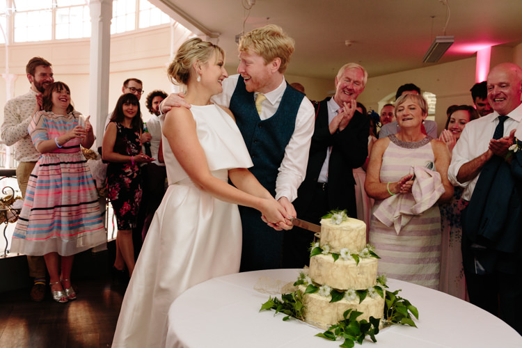 Bride Groom Cutting Cake Smiling White Green Chocolate Fudge Homemade Fresh Flowers Leaves | Modern Tropical Gold Urban Wedding https://www.christinewehrmeier.com/