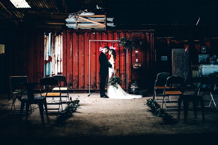 Ceremony Room Neon Sign Backdrop Metal Frame Foliage Edgy Raw Industrial Barn Wedding Ideas Greenery Festoon Lights http://www.two-d.co.uk/