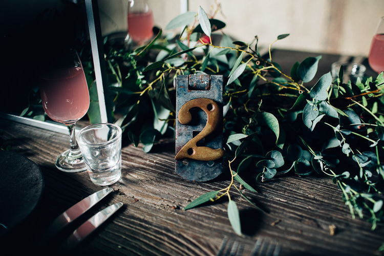 Table Names Edgy Raw Industrial Barn Wedding Ideas Greenery Festoon Lights http://www.two-d.co.uk/