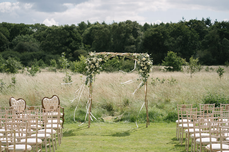 Outdoor Ceremony Arbour Arch Greenery White Floral Flowers Ribbons Relaxed Bohemian Summer Meadow Wedding https://karibellamy.com/