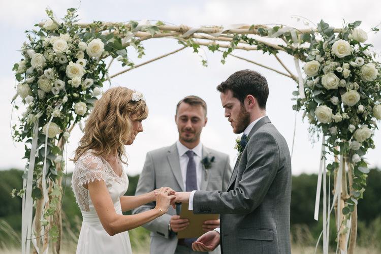 Outdoor Ceremony Arbour Arch Bride Bridal Rembo Styling Lace V Neck Dress Gown Hairpiece White Cream Rose Bouquet Eucalyptus Greenery Groom Groomsman Three Piece Grey Suit Relaxed Bohemian Summer Meadow Wedding https://karibellamy.com/