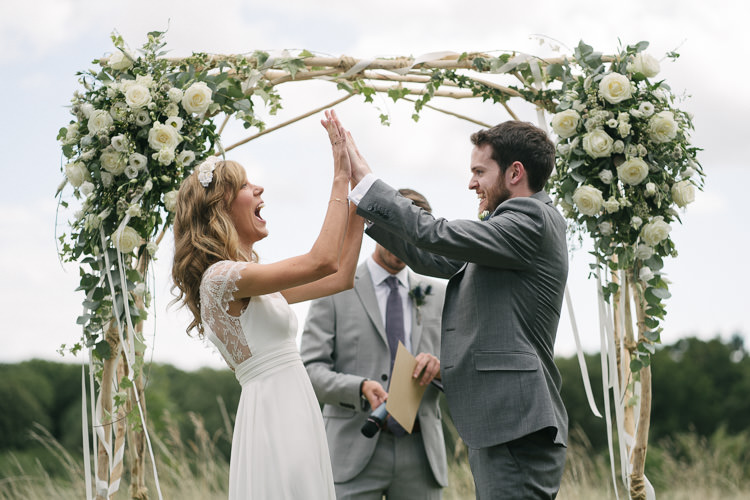 Outdoor Ceremony Arch Arbour Bride Bridal Rembo Styling Lace V Neck Dress Gown Hairpiece White Cream Rose Bouquet Eucalyptus Greenery Groom Groomsman Three Piece Grey Suit Relaxed Bohemian Summer Meadow Wedding https://karibellamy.com/