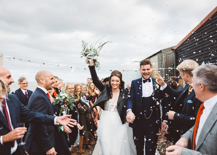 Bride Bridal Hayley Paige Dress Gown Tulle Princess Tuxedo Groom Waistcoat Navy Bow Tie Bouquet Ribbon Leather Jacket Confetti Shot Cool Stylish Windy Coastal Wedding East Quay Lobster Shack Whitstable http://holliecarlinphotography.com/