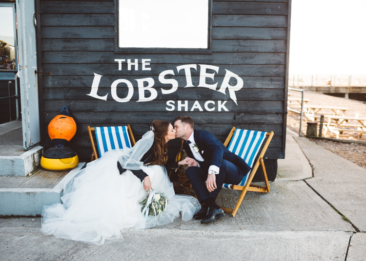 Bride Bridal Hayley Paige Dress Gown Tulle Princess Tuxedo Groom Waistcoat Navy Bow Tie Bouquet Ribbon Leather Jacket Deck Chairs Cool Stylish Windy Coastal Wedding East Quay Lobster Shack Whitstable http://holliecarlinphotography.com/