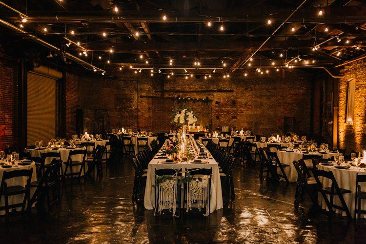 Warehouse Modern Refined Rustic Chic Festoon Lighting Black Chairs White Flowers | Boho Industrial Winter Wedding Lunalee Photography