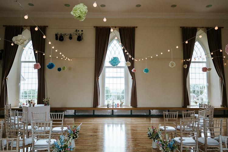 Ceremony Room Festoon Lights Pompoms Pretty Pastel Floral Village Hall Wedding Struve Photography