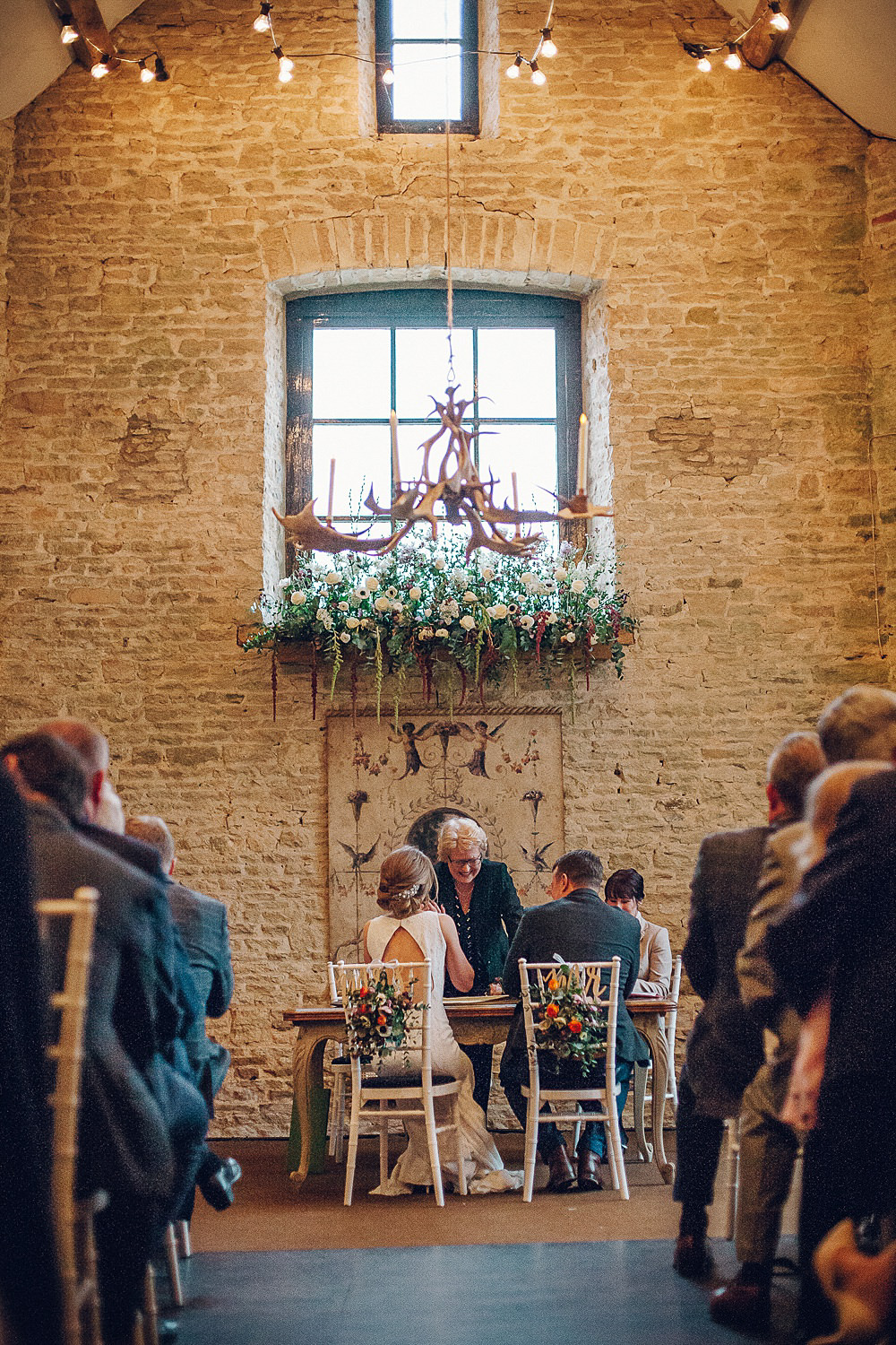 Bride Bridal Lace Boat Neck Cut Out Back Pronovias Neck Dress Tweed Groom Registry Table Floral Runner Chair Backs Navy Merriscourt Barn Wedding Cotswolds Katie de Silva Photography