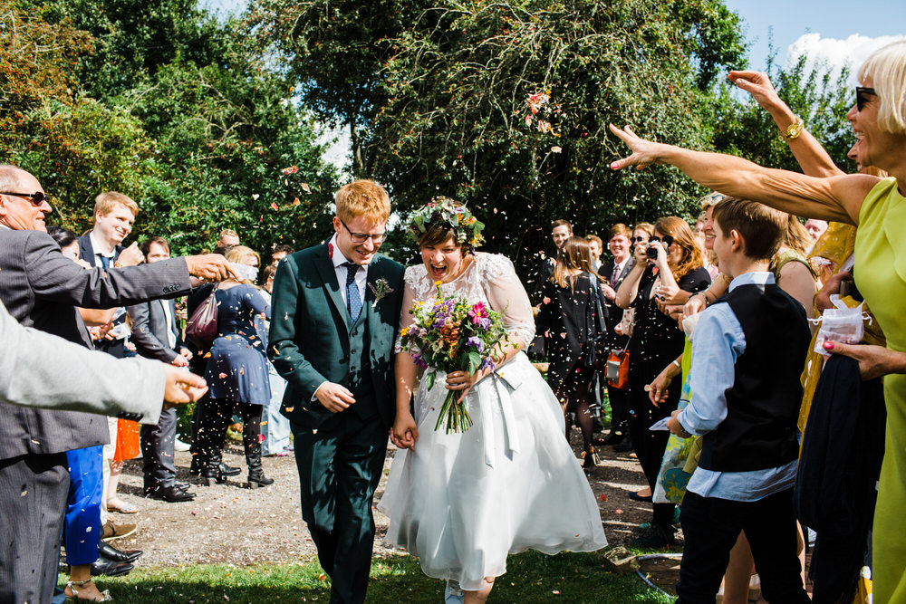 Bride Bridal Tea Length Sleeved Dress Flower Crown Multicoloured Bouquet Groom Bottle Green Suit Three Piece Confetti Secret Barn Sussex Wedding Rainbow Colourful Yvonne Lishman Photography