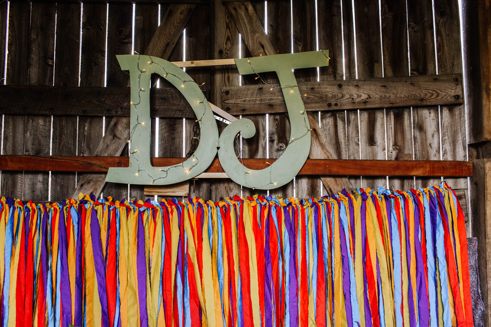 Initials Fairy Lights Coloured Streamers Backdrop Decor Secret Barn Sussex Wedding Rainbow Colourful Yvonne Lishman Photography