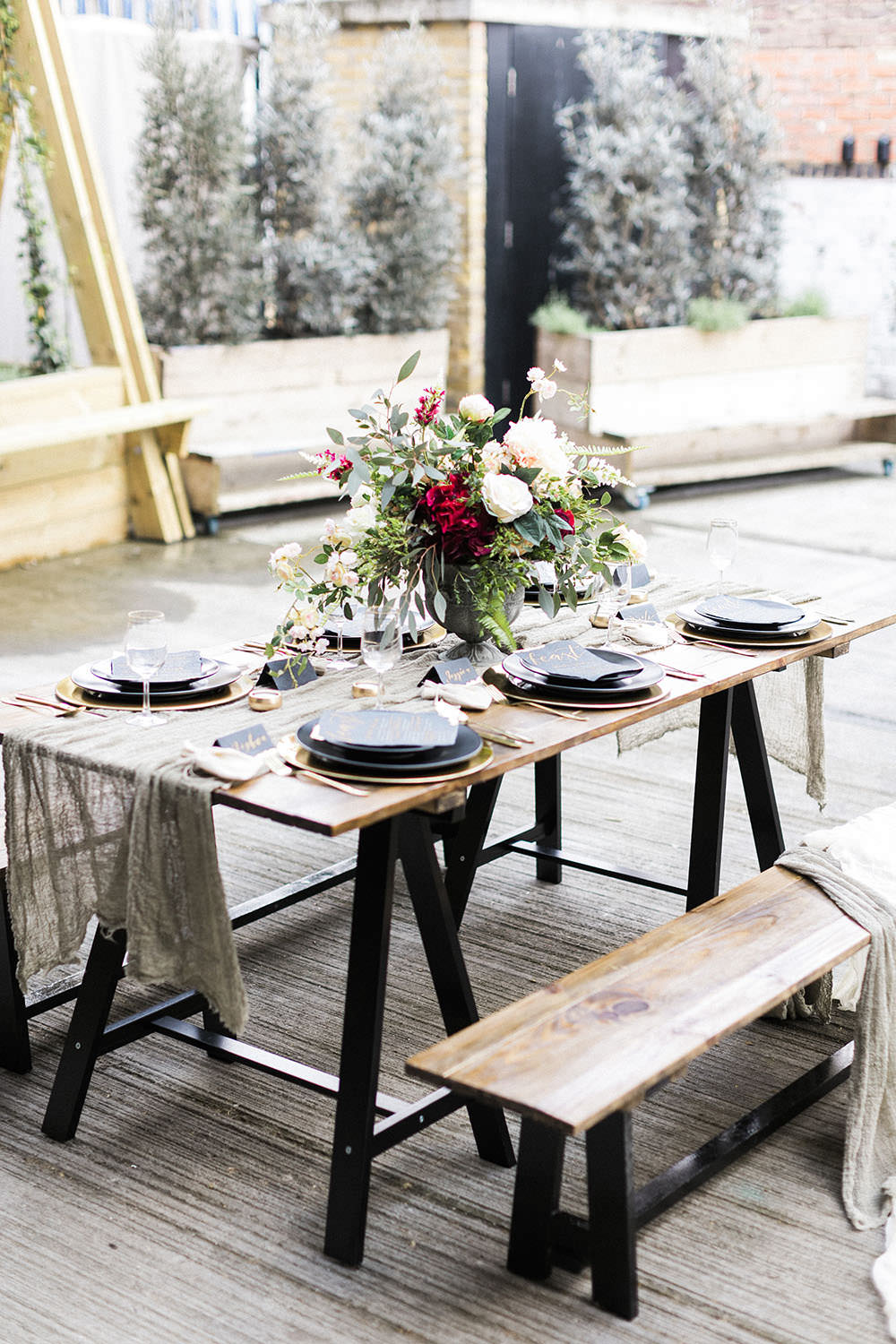 Tablescape Decor Muslin Linen Table Cloth Trestle Table Flowers Black Charger Plates Burgundy Gold Wedding Ideas Sarah Porter Photography