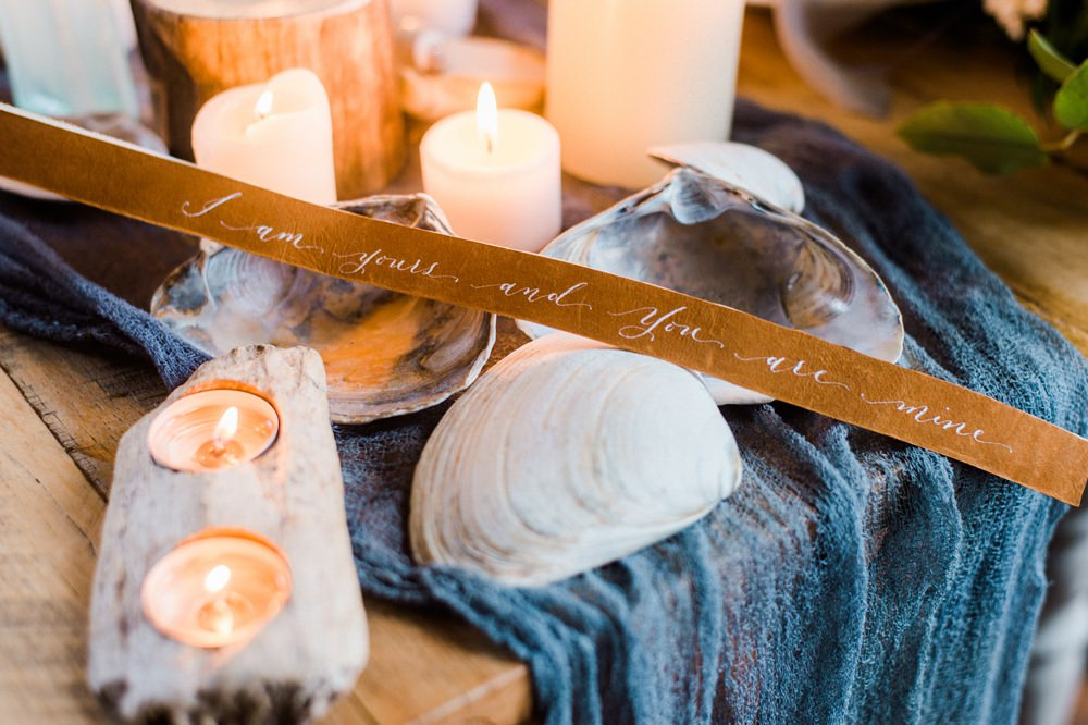 Nature Inspired Styled Shoot Seashell Tablescape Candles Grey Blue Gold Crystal Glasses Silk Ribbon Driftwood   Ocean Wedding Ideas Industrial Rachel Watkinson Photography