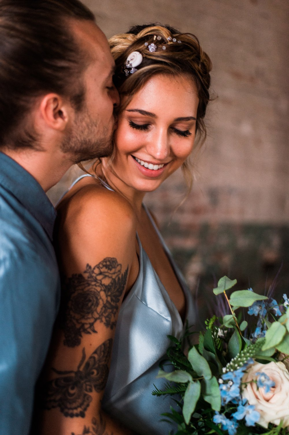 Nature Inspired Styled Shoot Seashell Headpiece Updo Tattooed Bride Blue Dress Casual Groom Blue Shirt Pastel Bouquet Kiss | Ocean Wedding Ideas Industrial Rachel Watkinson Photography