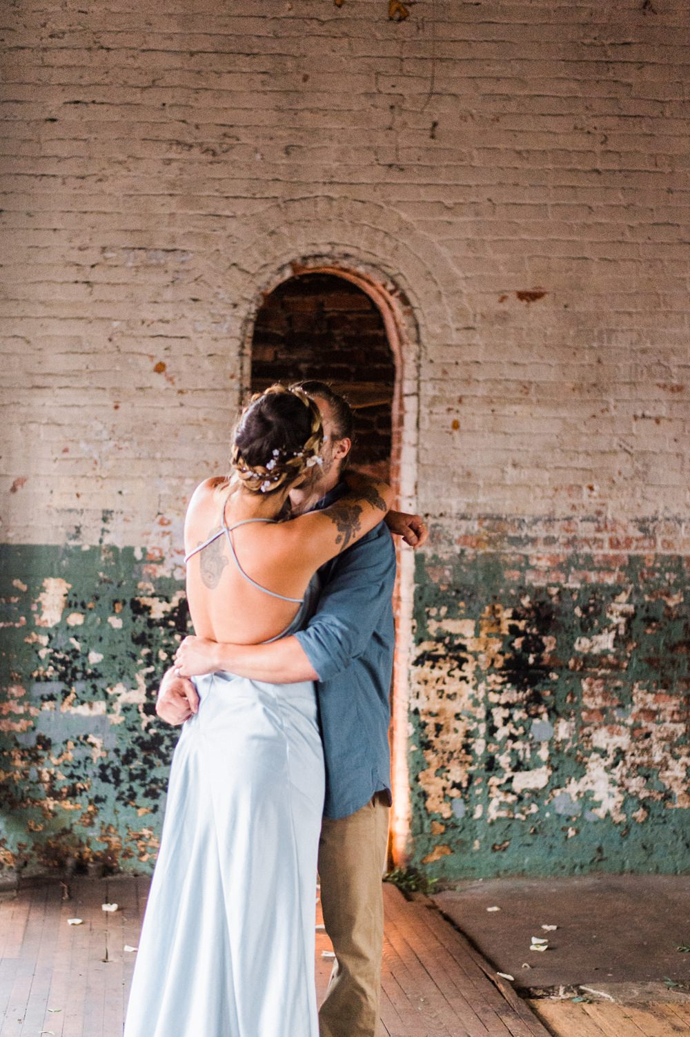 Nature Inspired Styled Shoot Seashell Headpiece Updo Tattooed Bride Blue Dress Casual Groom Blue Shirt Kiss | Ocean Wedding Ideas Industrial Rachel Watkinson Photography