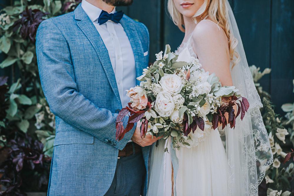 Secret Dresshouse Ethereal Bride Bridal Gown Blue Linen Jacket Bow Tie Groom Leaf Foliage Flower Florals River Romance Wedding Ideas Mindy Coe Photography