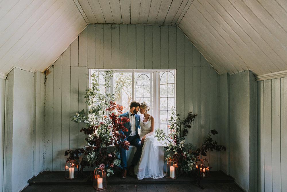 Secret Dresshouse Ethereal Bride Bridal Gown Blue Linen Jacket Bow Tie Groom Leaf Foliage Flower Florals Storm Hurricane Lanterns Candles River Romance Wedding Ideas Mindy Coe Photography