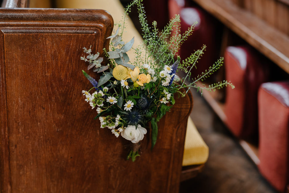 Outdoor Farm Field Marquee Yellow Blue Green Wildflowers Church Pew Decoration Ceremony | Rustic and Relaxed Spring Tipi Wedding Inbetween Days Photography