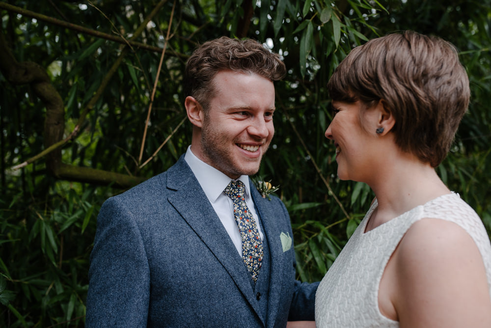 Outdoor Farm Field Marquee Groom Bride Pixie Cut Blue Suit Modern Green Yellow Buttonhole | Rustic and Relaxed Spring Tipi Wedding Inbetween Days Photography