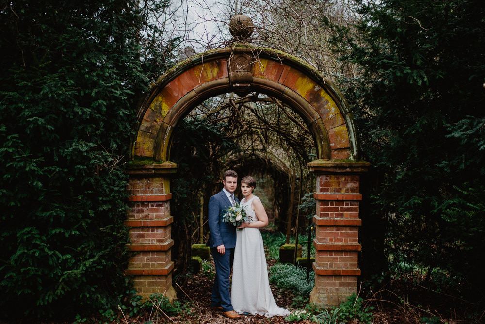 Outdoor Farm Field Marquee Groom Bride Arch Blue Suit Modern Green Yellow Bouquet | Rustic and Relaxed Spring Tipi Wedding Inbetween Days Photography
