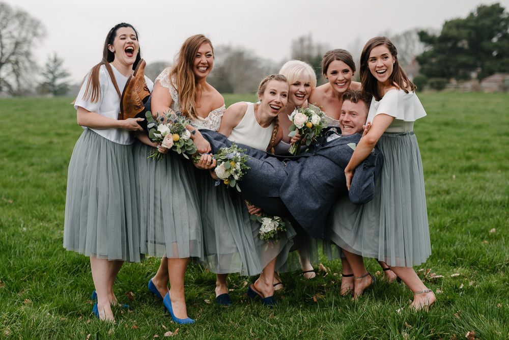 Outdoor Farm Field Marquee Bridesmaids White Grey Separates Group Holding Groom | Rustic and Relaxed Spring Tipi Wedding Inbetween Days Photography