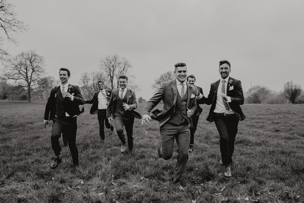 Outdoor Farm Field Marquee Groom Groomsmen Blue Navy Suits Funny Running | Relaxed and Rustic Spring Tipi Wedding Inbetween Days Photography