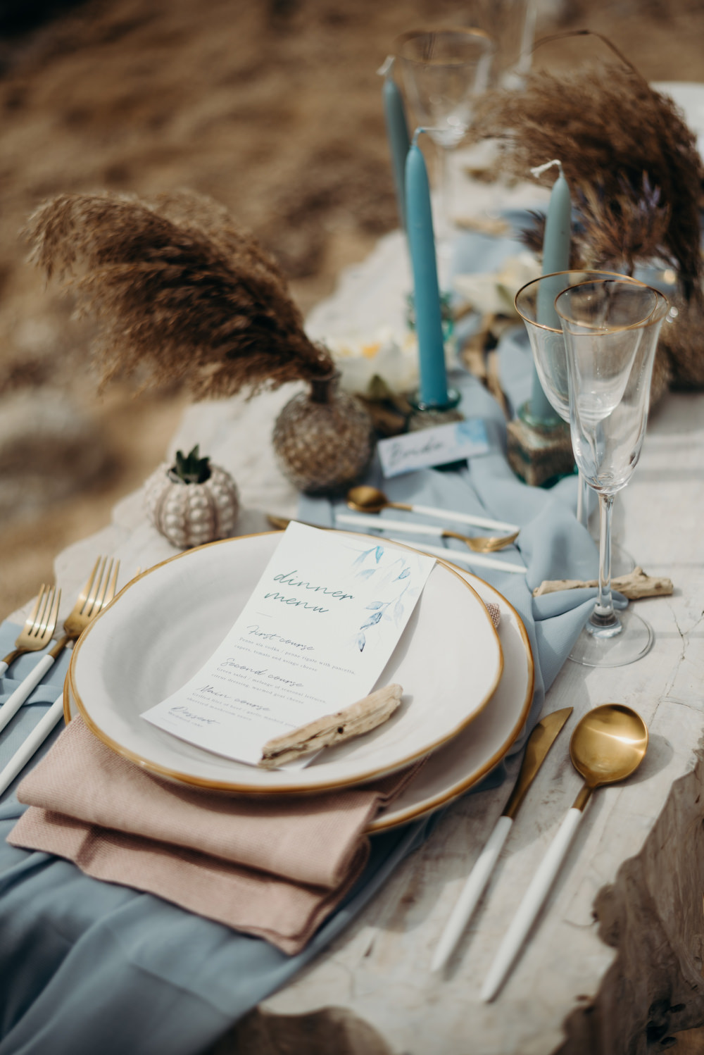 Outdoor Wild Nature Destination Spain Europe Coastal Styled Shoot Beach Table Elegant Styling Menu Candles Cutlery | Blue Ibiza Elopement Ideas and Surprise Proposal Serena Genovese Photography