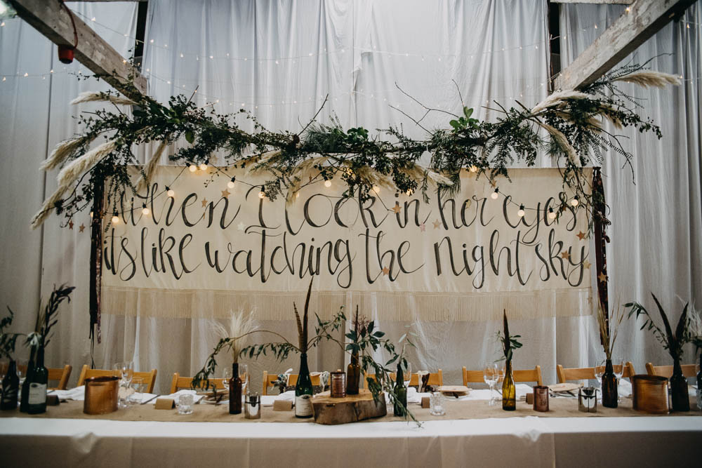 Top Table Back Drop Greenery Pampas Grass Brush Lettering Feathers Bottles Wood Tree Slice Railway Barn Wedding Lottie Photography