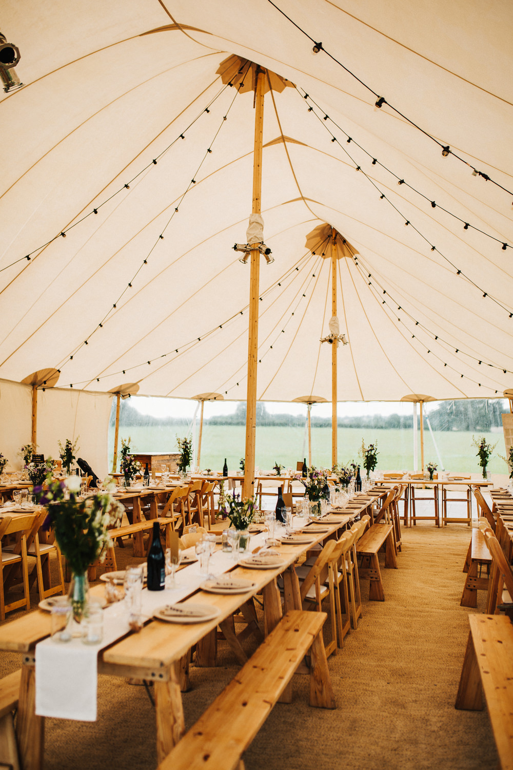 Wooden Tables Benches Chairs Festoon Lighting Whimsical Countryside Sperry Tent Wedding Emilie May Photography
