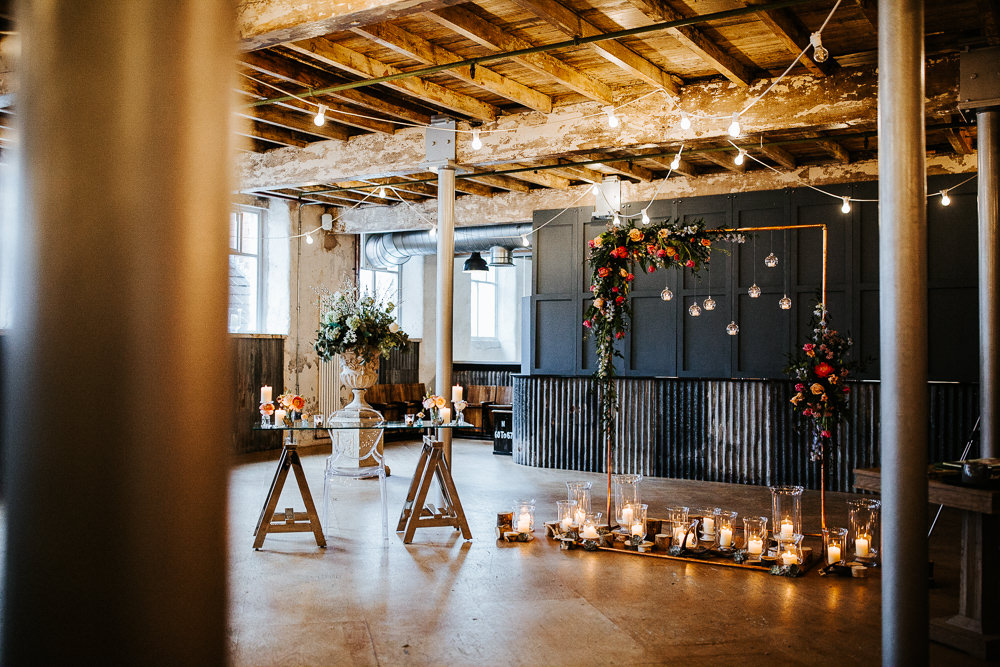Ceremony Warehouse Industrial Festoon Lights Flowers Backdrop Arch Aisle Holmes Mill Wedding Emilie May Photography