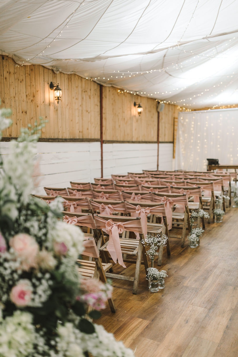 Ceremony Room Drapes Fairy Lights Ceiling Flowers Aisle Arch Floral Pink Greenery Ribbon Chairs Wellbeing Farm Wedding Anna Wood Photography