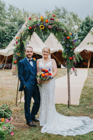 Mori Lee Dress Gown Bride Bridal Train Lace Flower Arch Backdrop Greenery Foliage Flowers Sunflowers Rose Colourful Tipi Wedding Charlotte Razzell Photography