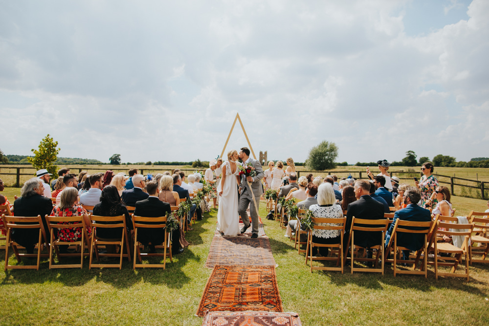 Aisle Ceremony Outdoor Persian Rug Wooden Triangle Backdrop Palm Plants Godwick Great Barn Wedding Joshua Patrick Photography