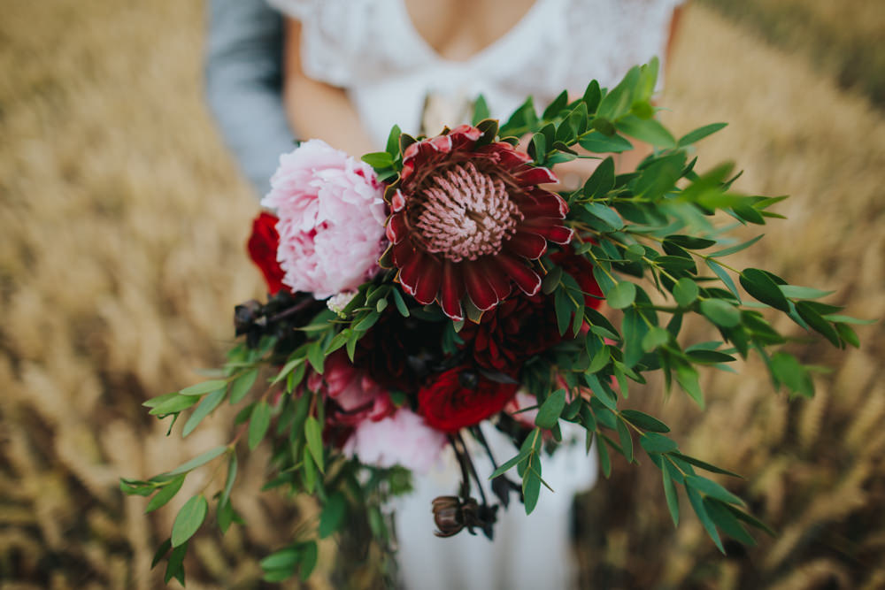 Bouquet Flowers Bride Bridal Red Greenery Foliage Ribbons Peony Peonies Rose Proteas Pink Godwick Great Barn Wedding Joshua Patrick Photography