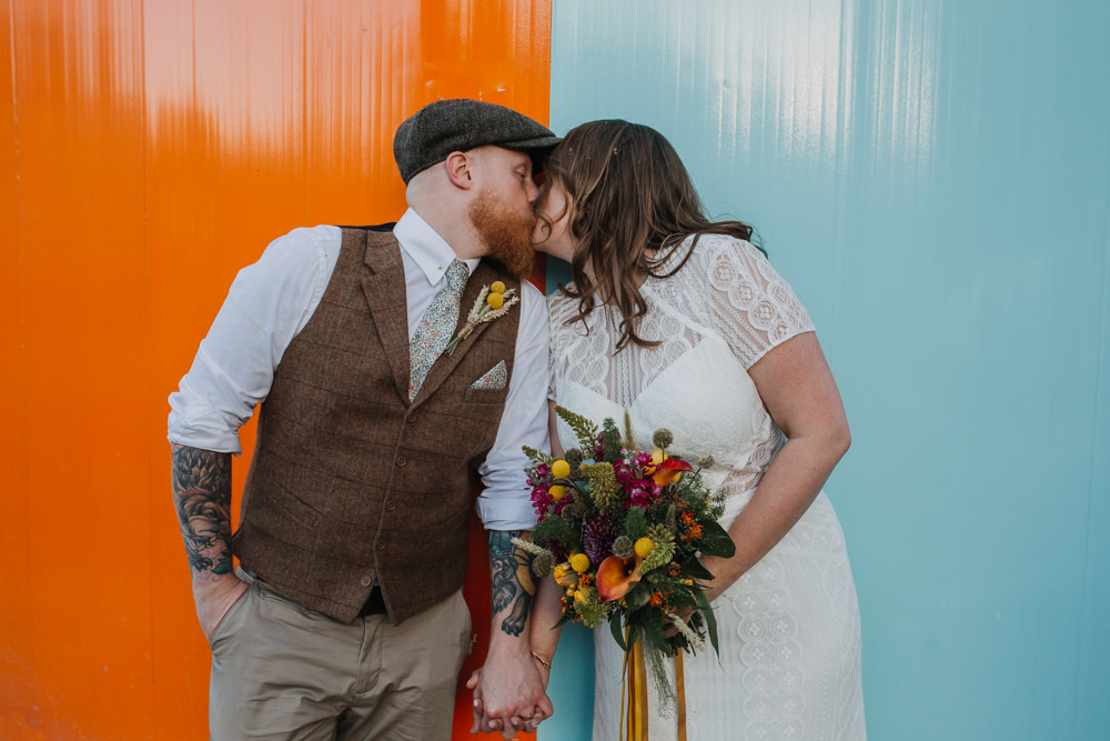 Bride Bridal High Neck Short Sleeve Lace Dress Sweetheart Neckline Waistcoat Tweed Chinos Groom Liberty Print Tie Flat Cap Multicoloured Bouquet Ribbon The Chimney House Wedding Ellie Grace Photography