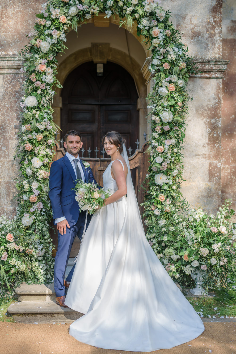 Floral Archway Entrance Bride Bridal A Line Dress Straps Sleeveless Silk V Neck Blue Suit Groom Veil Babington House Wedding Ria Mishaal Photography