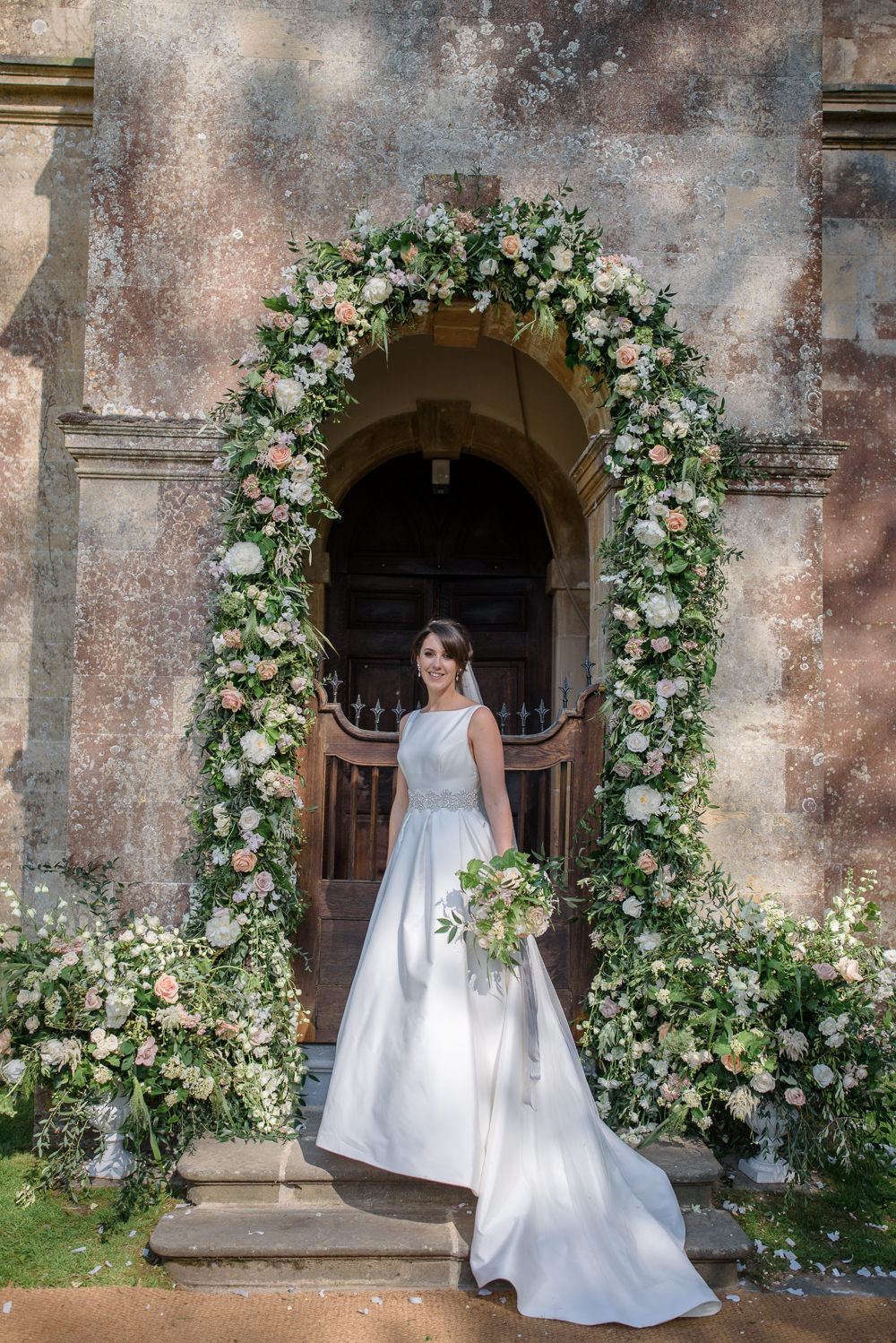 Bride Bridal A Line Dress Straps Sleeveless Silk Boat Neck Veil Entrance Archway Floral Flowers Bouquet Silk Ribbon Babington House Wedding Ria Mishaal Photography