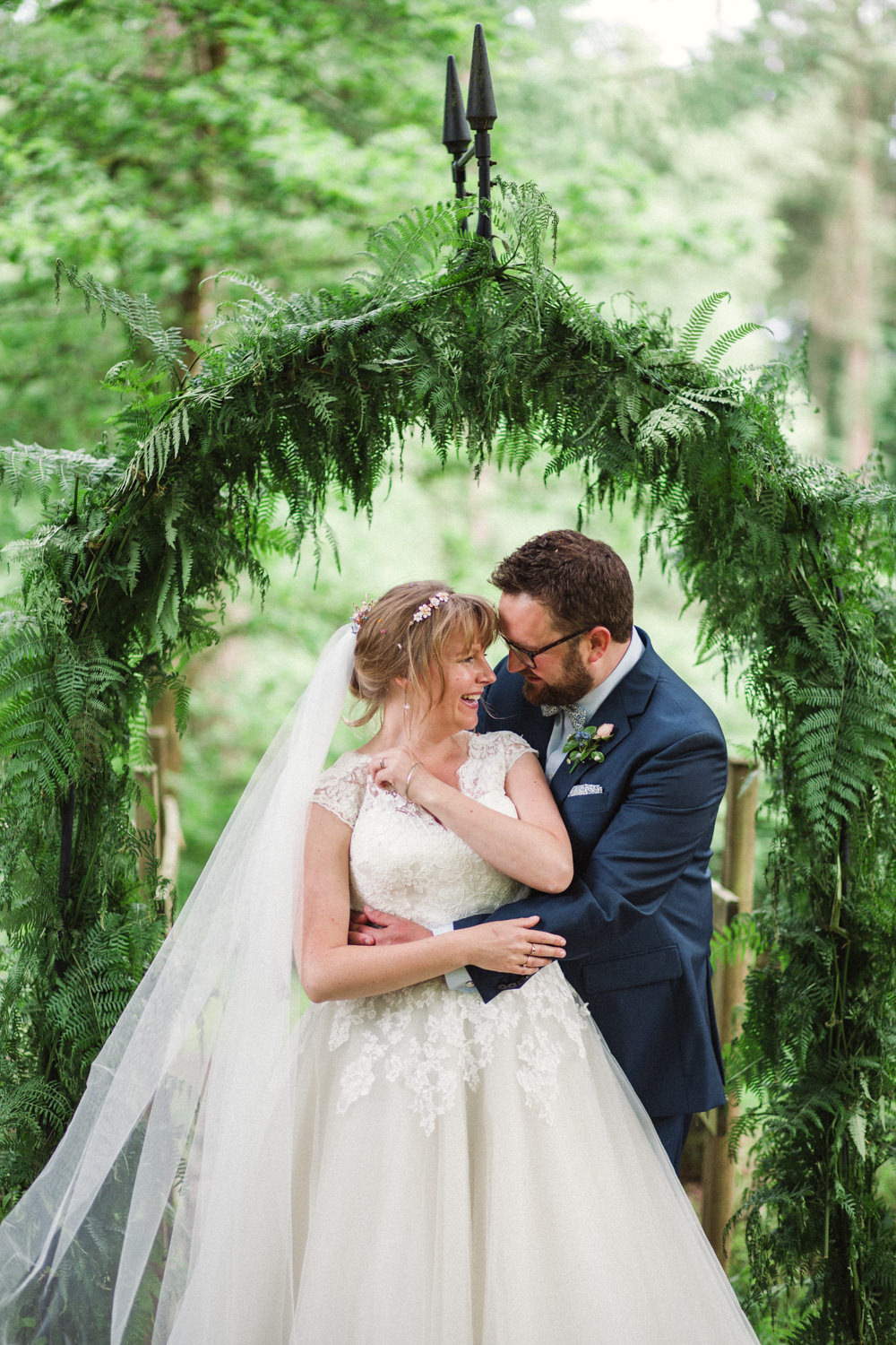 Bride Bridal Ballerina Length Dress Lace Sleeves Navy Suit Groom Veil Greenery Foliage Archway Middle Coombe Farm Wedding Emma Stoner Photo