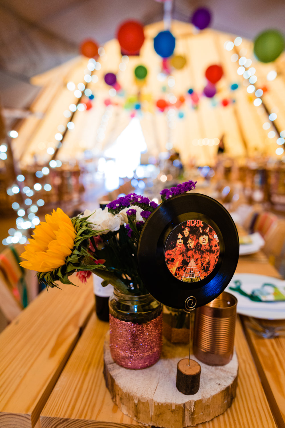 Centrepiece Decor Log Table Tine Jar Flowers Vinyl Table Name Number Colourful Festival Party Wedding Emma and Rich Photography